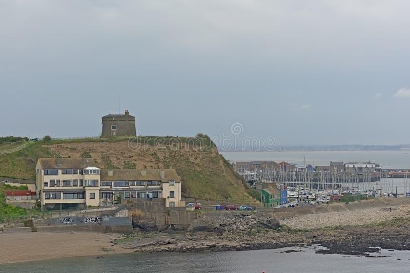 Puerto de Howth con el barco de navegación y torre de Martello en un acantilado foto de archivo