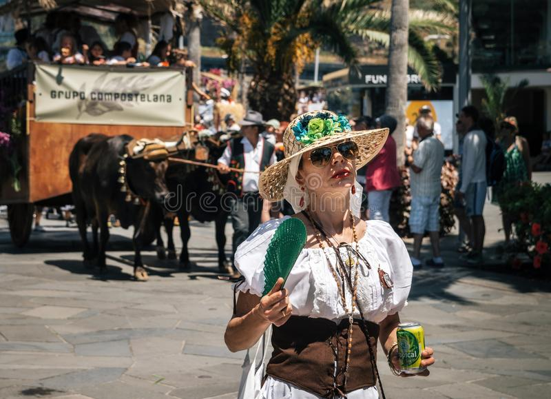 The expressive woman celebrates The Day of the Canary islands. Puerto de la Cruz, Tenerife, Canary Islands, Spain - May 30, 2017: Expressive woman with fan in royalty free stock images