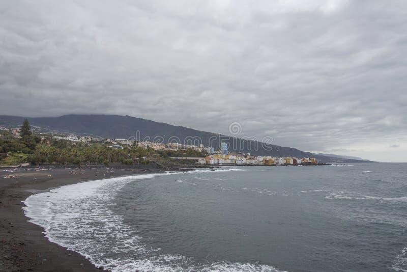 Puerto de la Cruz, Tenerife, Ilhas Canárias - a vista de casas coloridas, o mar e a vulcânico-areia encalham Praia preta em tener imagens de stock