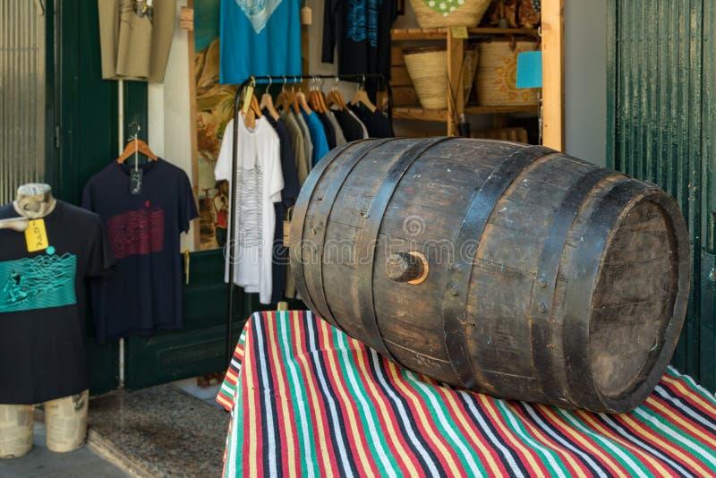 Puerto de la Cruz Tenerife, Spanien - Juli 10, 2019: En gammal vinfat ligger på en tabell som täckas med en bordduk av typisk arkivfoton