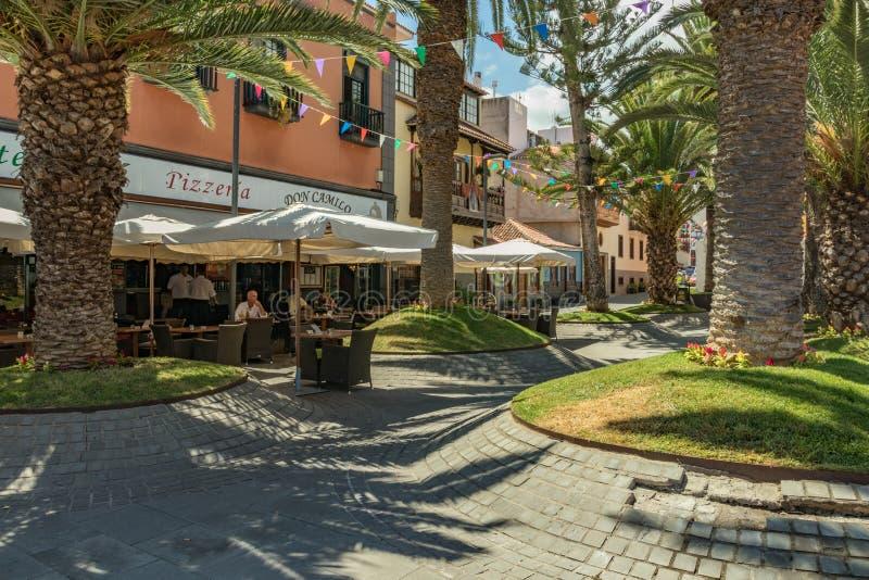 Puerto de la Cruz, Teneriffa, Spanien - 10. Juli 2019: Bunte Häuser und Palmen auf Straßen Leute entspannen sich und haben Spaß a stockfoto