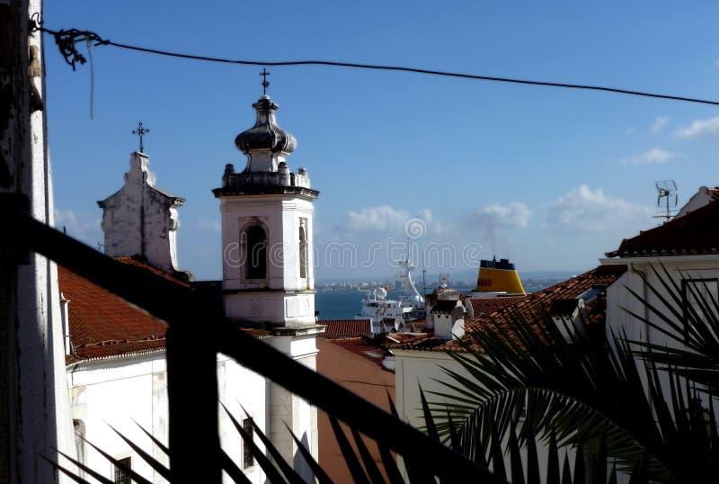 Puerto de Lisboa con los tejados marrones de la arcilla, la iglesia blanca y el barco imagenes de archivo