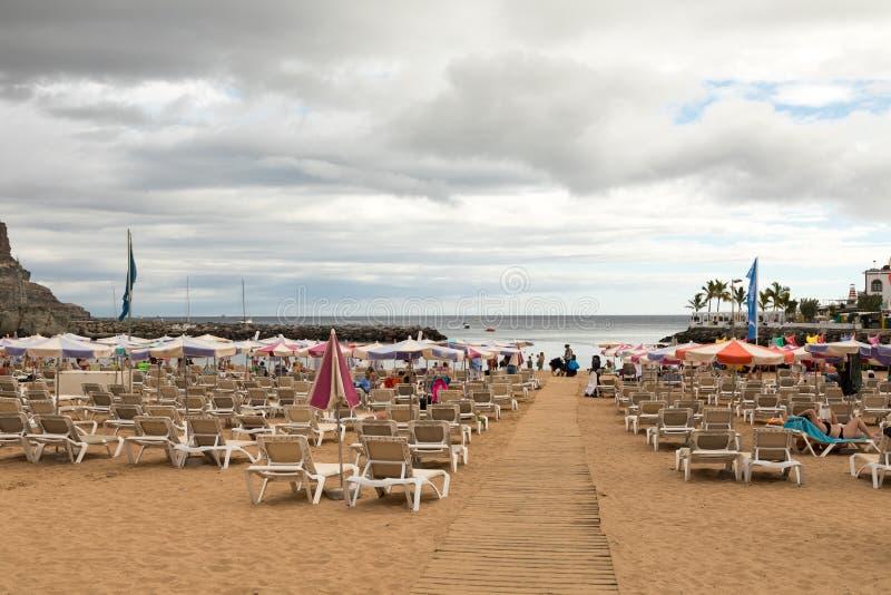 Puerto DE Mogan, Gran Canaria in Spanje - December 16, 2017: Sunbeds en parasols op het strand, met een raadsgang in royalty-vrije stock foto's