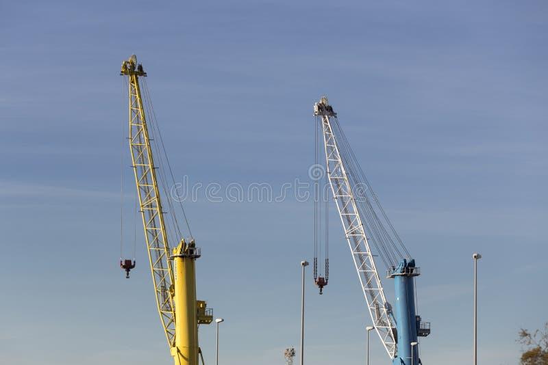Puerto de Sagunto, dos grúas, una amarilla y una azul fotografía de archivo libre de regalías