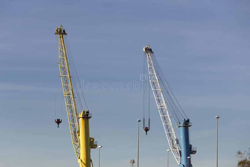 Puerto de Sagunto, due gru, una gialla ed una blu fotografia stock libera da diritti