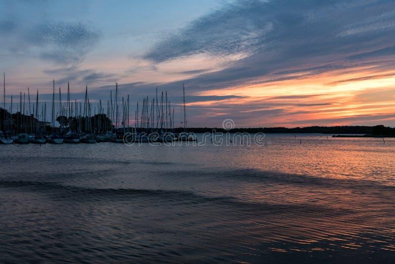Puerto del bote pequeño con los barcos de navegación en luz del sol rosada de la tarde foto de archivo libre de regalías