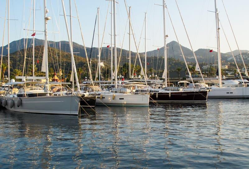 Puerto deportivo pintoresco con los veleros y los barcos en el fondo de montañas Yalikavak Turquía imagenes de archivo