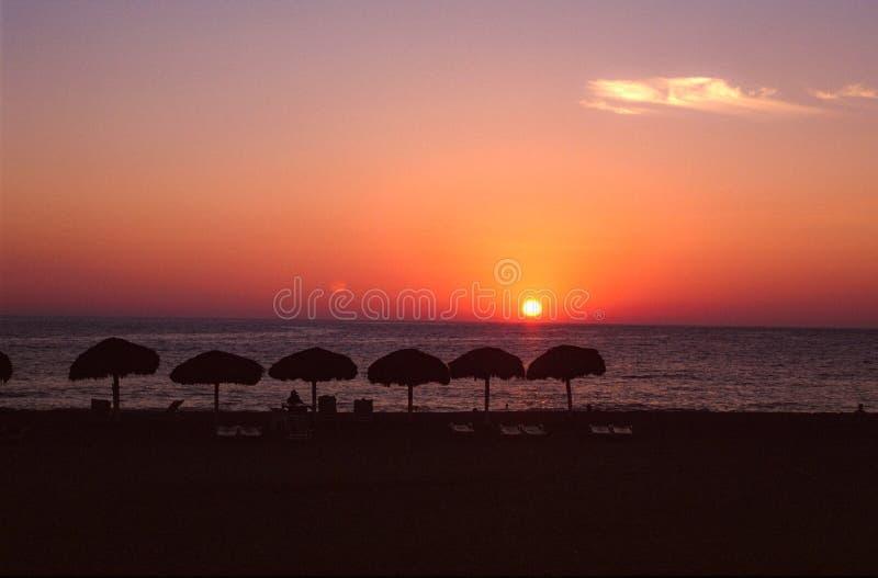 Puerto Escondido, Mexico: Solinställning över havet med månen redan i himlen royaltyfri fotografi