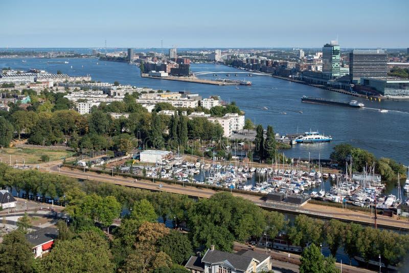 Puerto holandés Amsterdam de la visión con las construcciones del puerto deportivo, del transbordador y de viviendas imagenes de archivo