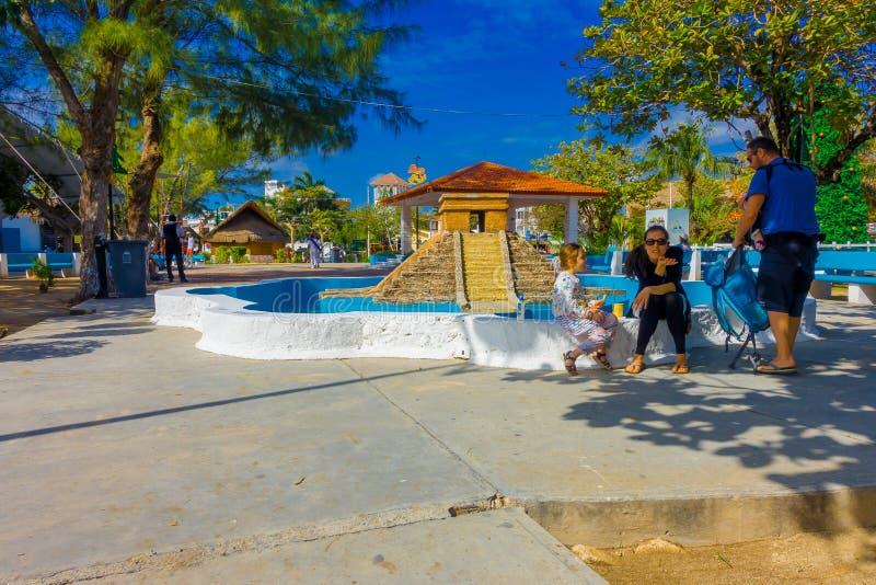 Puerto Morelos Meksyk, Styczeń, - 10, 2018: Niezidentyfikowani ludzie siedzi w granicie drylująca pusta fontanna obraz stock