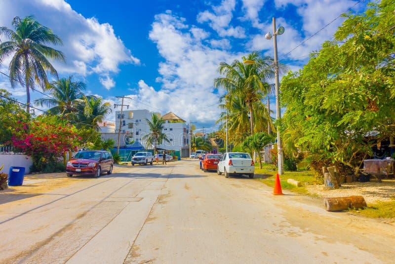 Puerto Morelos Meksyk, Styczeń, - 10, 2018: Plenerowy widok niektóre domy z wiele samochodami parkującymi w ulicie Puerto zdjęcia stock