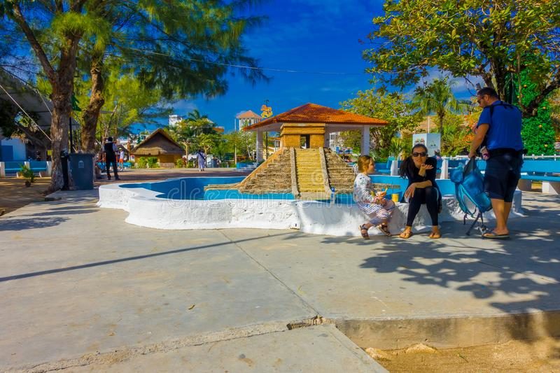 Puerto Morelos, Mexico - January 10, 2018: Unidentified people sitting in the border of a stoned empty fountain of. Pyramid of yucatan in the middle of the park stock image