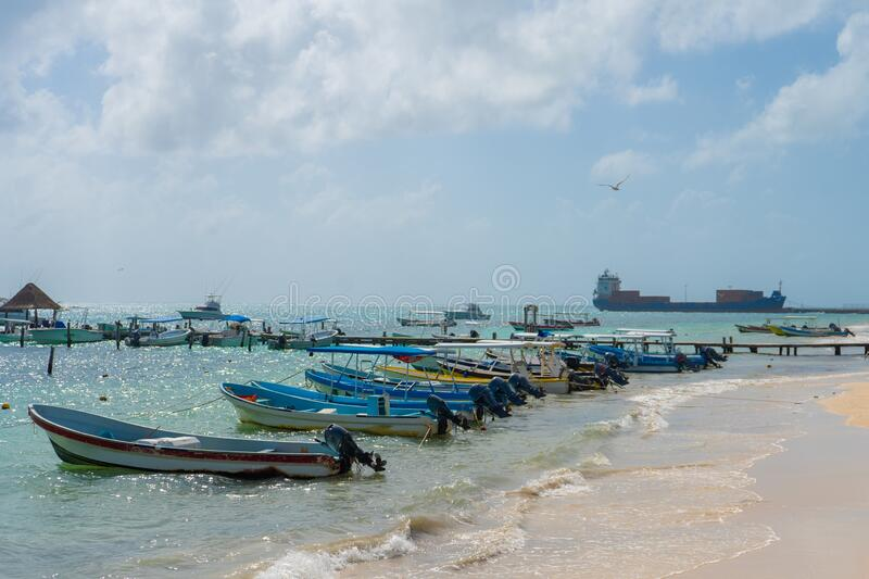 Puerto Morelos seaside view with sea and boats. Caribbean sky with clouds. White sand shore. Background or wallpaper. Yucatan. Qui royalty free stock photo