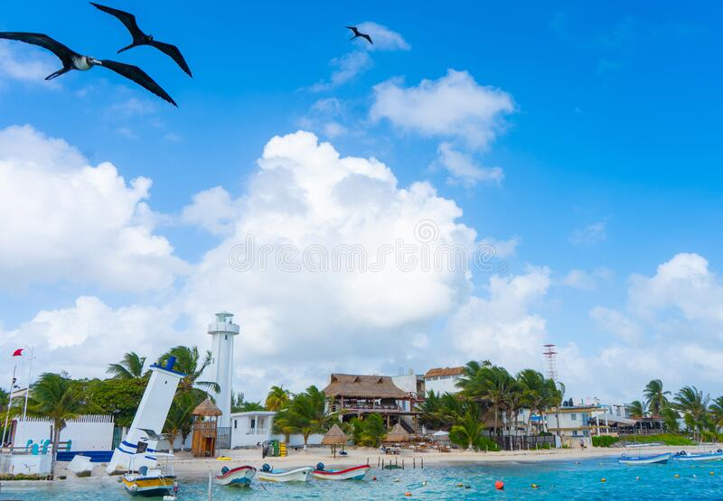 Puerto Morelos seaside view with sea, lighthouse, birds and boats. Caribbean sky with clouds. White sand shore. Background or wall. Paper. Yucatan. Quintana roo stock photos
