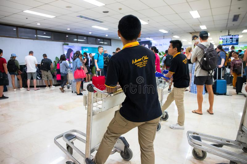 Puerto Princesa, Филиппины - 30-ое ноября 2018: туристская несущая толпы и вагонетки в аэропорт Группа обеспечения обслуживания а стоковые фотографии rf