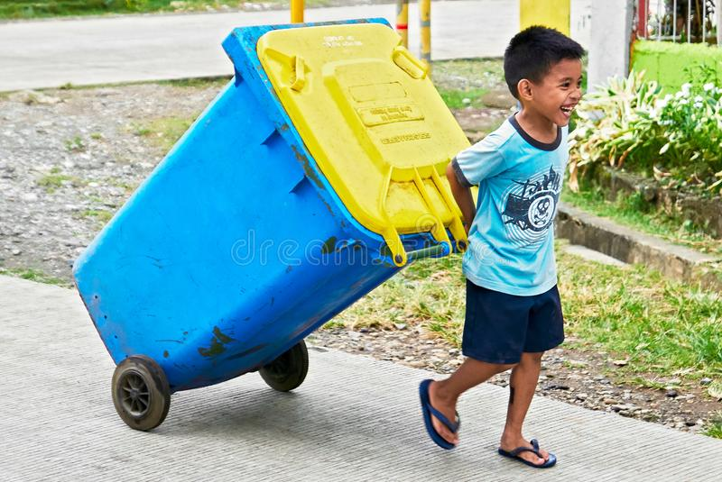 One small young smiling boy pulling a garbage container royalty free stock photos