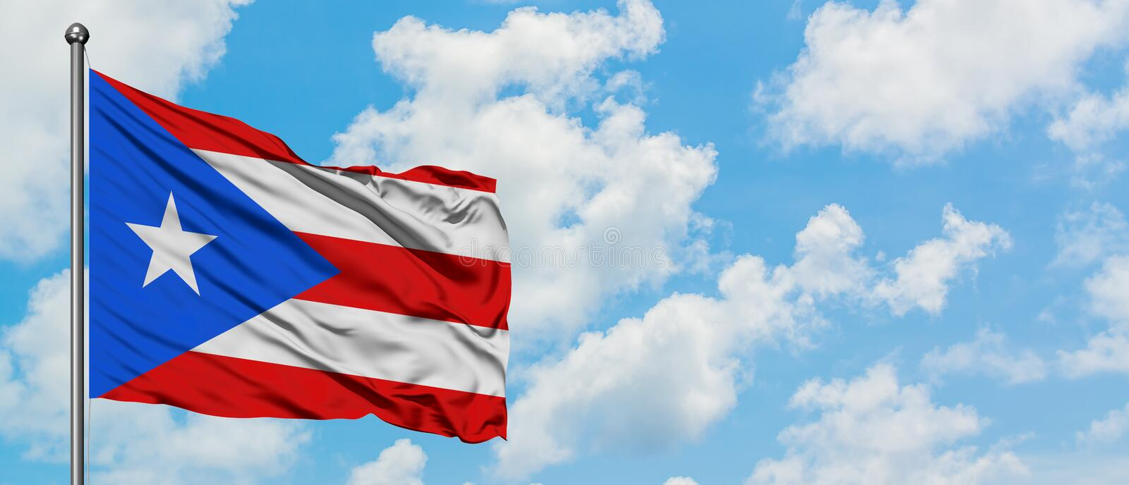 Puerto Rico flag waving in the wind against white cloudy blue sky. Diplomacy concept, international relations.  royalty free stock photo
