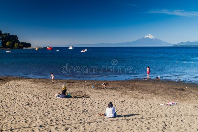 PUERTO VARAS, O CHILE - 23 DE MARÇO: Povos em um bach do lago Llanquihue na cidade de Puerto Varas Vulcão de Osorno no fundo foto de stock royalty free