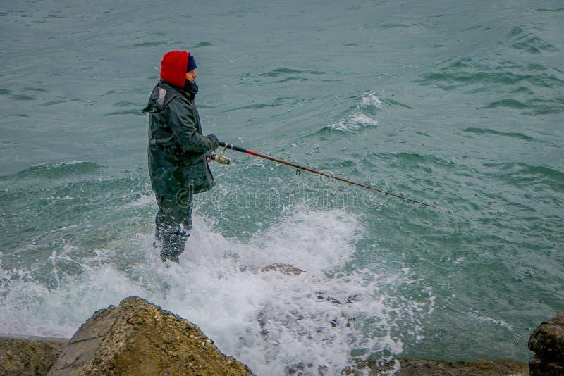 PUERTO VARAS, O CHILE, SETEMBRO, 23, 2018: Pescador não identificado que está em uma rocha com uma vara de pesca no chileno fotografia de stock