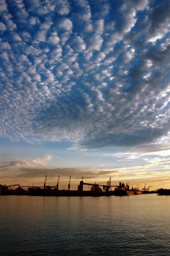 Puerto y cielo en la puesta del sol imagen de archivo