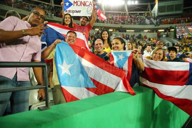 Puertoricanska fans stöttar den olympic mästaren Monica Puig av Puerto Rico under tenniskvinnors finalen för singlar av Rio de Ja arkivbilder