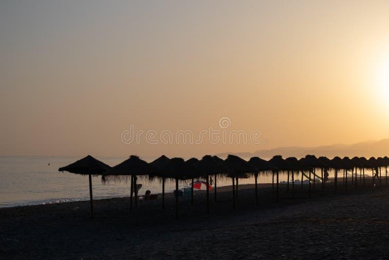 Puesta de sol en la playa llena de sombrillas de paja en Salobreña, Granada, España imagenes de archivo