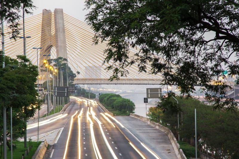 Puesta de sol, luces y vehículos en tránsito Carretera de la ciudad de Sao Paulo al lado del río fotos de archivo libres de regalías