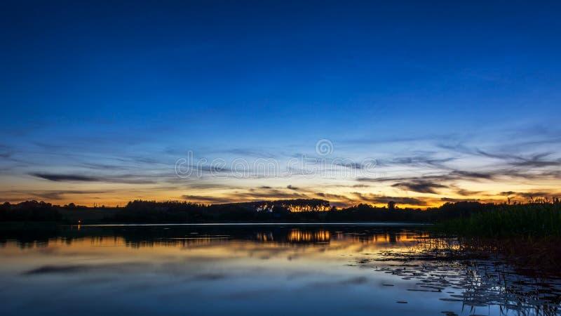 Puesta de sol nubosa en un tranquilo solsticio de verano en el lago Zirnajai en Lituania fotos de archivo libres de regalías