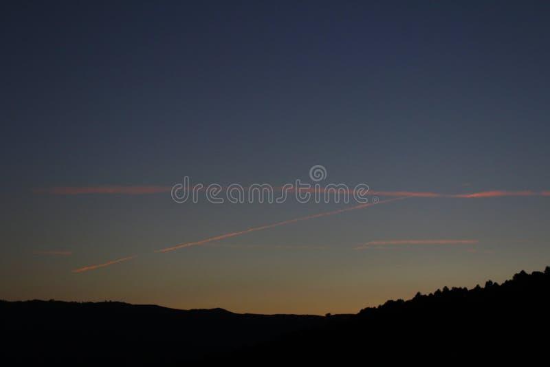 puesta del sol agradable con la estela de varios aviones fotografía de archivo libre de regalías
