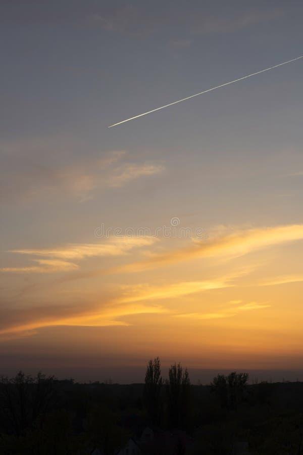 puesta del sol Amarillo-azul en el fondo de una ciudad oscura imagen de archivo