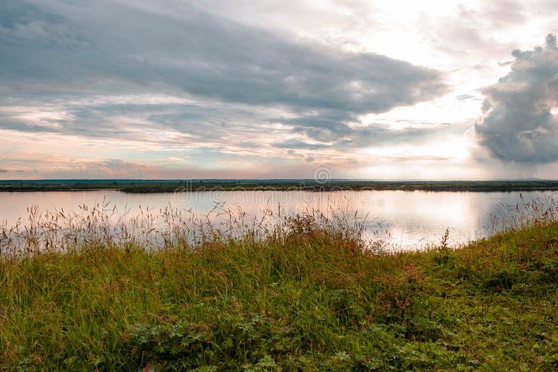 Puesta del sol anaranjada azul del rosa hermoso dramático en el río con la reflexión y las nubes en fondo natural imagen de archivo