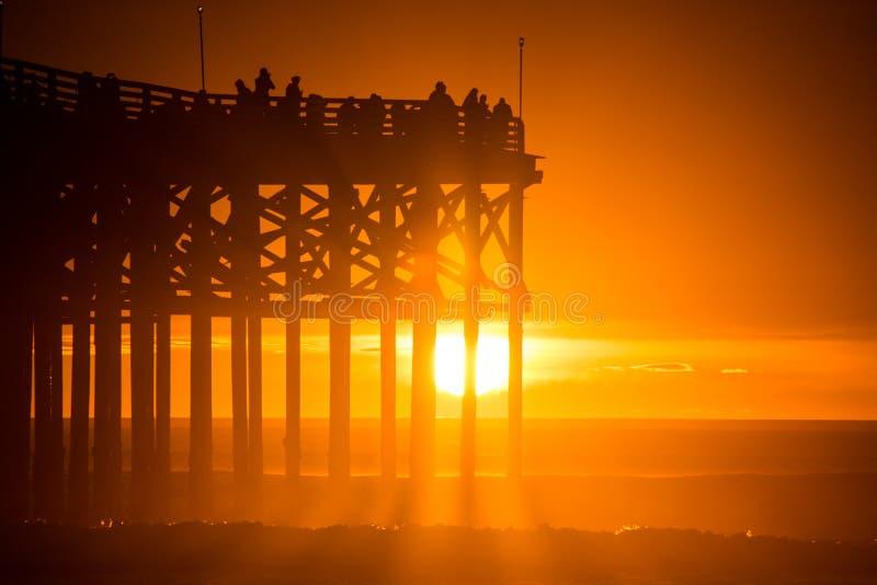 Puesta del sol anaranjada en la playa con el embarcadero Sombra del embarcadero y de la gente en el embarcadero imagenes de archivo