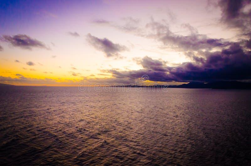 Puesta del sol anaranjada intensa en la playa tropical aislada telecontrol imagenes de archivo