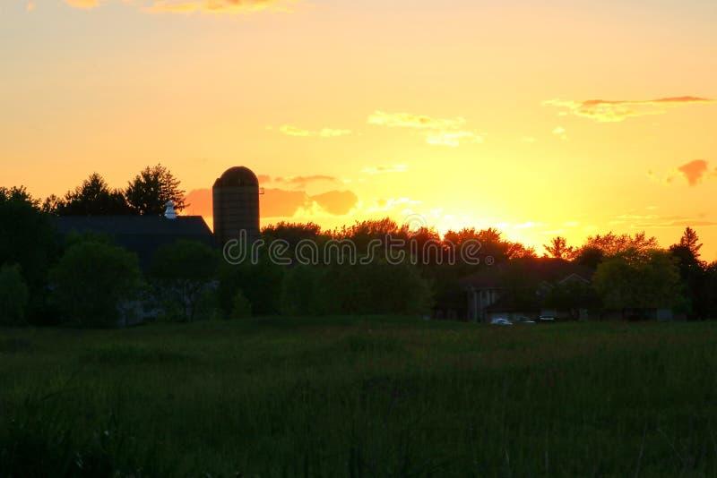 Puesta del sol anaranjada sobre tierras de labrantío en Wisconsin fotos de archivo