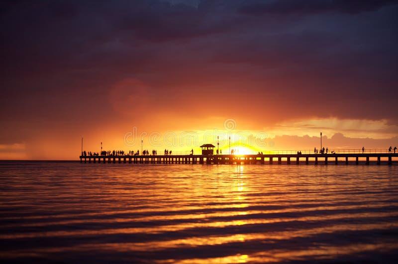 Puesta del sol anaranjada y púrpura sobre el peir de madera foto de archivo