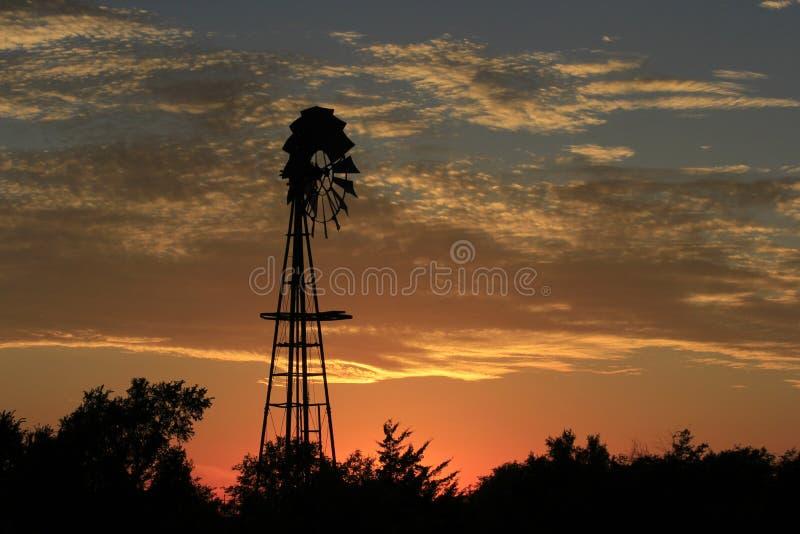 Puesta del sol ardiente de Kansas con una silueta del molino de viento y un cielo colorido fotos de archivo libres de regalías