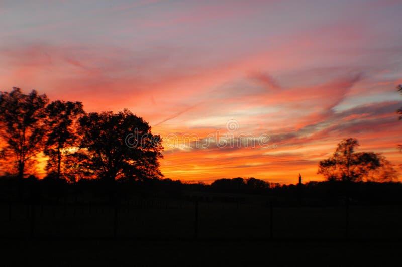 Puesta del sol ardiente en el cielo imagenes de archivo