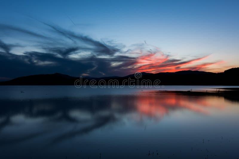 Puesta del sol ardiente sobre el lago Jrebchevo foto de archivo