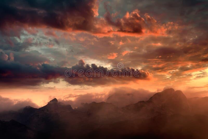 Puesta del sol ardiente y picos de montaña nebulosos fotografía de archivo libre de regalías
