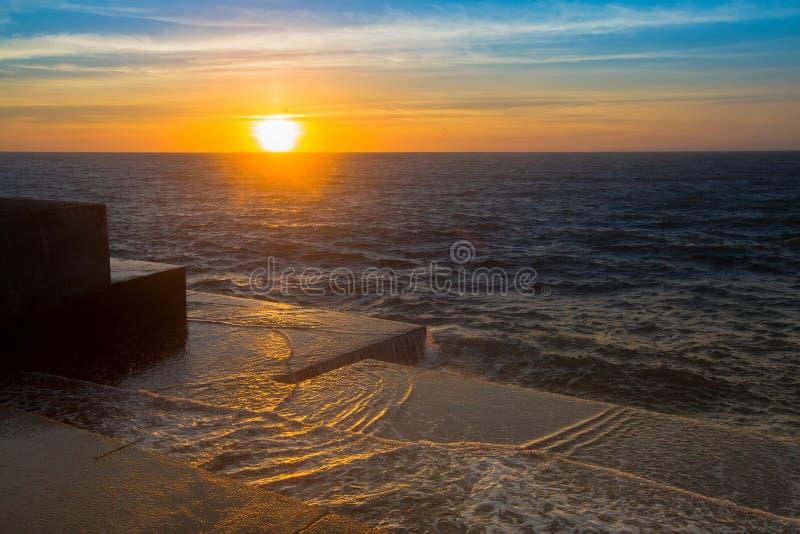 Puesta del sol asombrosa del mar en el embarcadero de piedra en tiempo tranquilo Naturaleza fotos de archivo