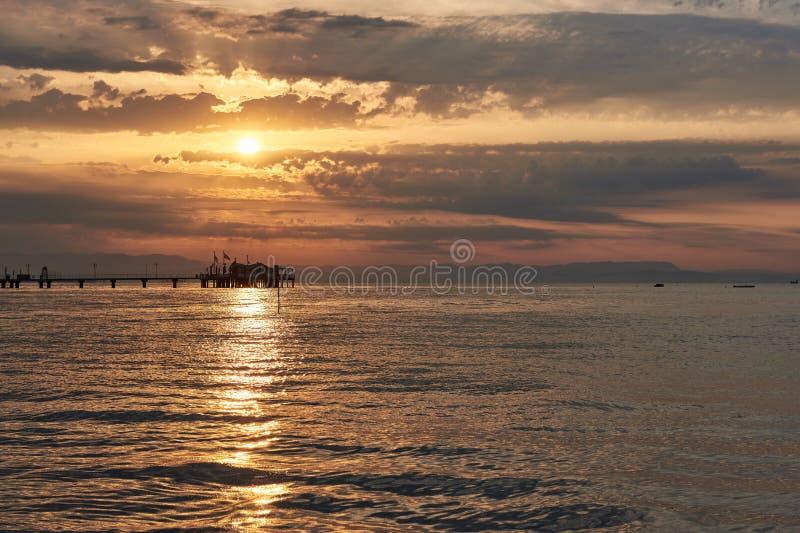 Puesta del sol asombrosa en el mar Mar adriático con la orilla Lignano Sabbiadoro, Italia imágenes de archivo libres de regalías