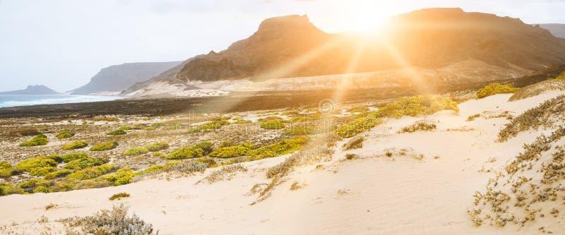 Puesta del sol asombrosa sobre las montañas volcánicas en los rayos solares atlánticos desolated de la costa que caen en el sao c imagen de archivo libre de regalías