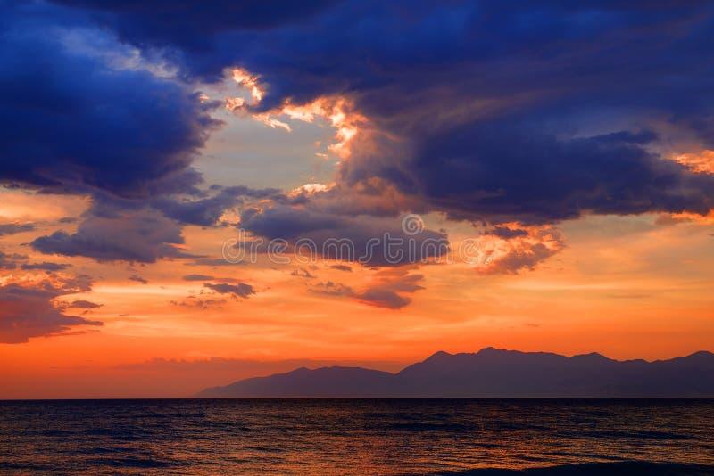 Puesta del sol azul anaranjada roja colorida romántica dramática misteriosa hermosa de la oscuridad del sol en el mar jónico en l imágenes de archivo libres de regalías