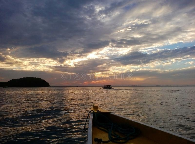 Puesta del sol del barco que se acerca a Abad Santos Island en las islas parque nacional, Alaminos, Philippinnes de Hundreed imagenes de archivo