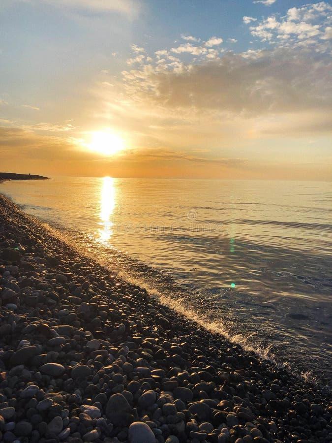 Puesta del sol brillante amarilla hermosa en el mar, r?o, lago, charca, agua en la playa rocosa de un centro tur?stico caliente t imagen de archivo