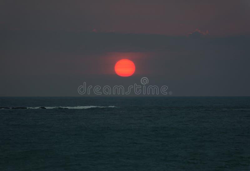 Puesta del sol brillante con el sol rojo grande bajo superficie del océano imagen de archivo