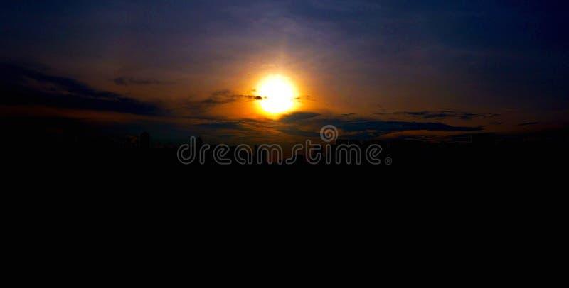 Puesta del sol brillante detrás del horizonte de la ciudad imagenes de archivo