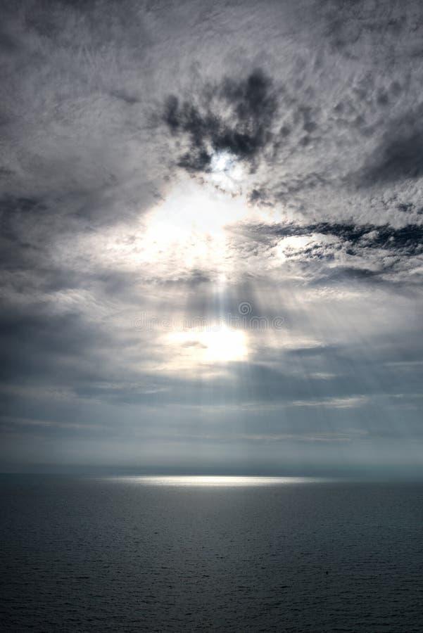 Puesta del sol brillante en cielo azul con las nubes sobre luz del rayo del mar foto de archivo