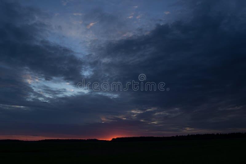 Puesta del sol brillantemente ardiente en un campo con las nubes grises fotos de archivo libres de regalías