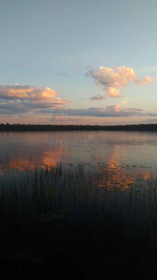 Puesta del sol carmesí sobre el lago del espejo foto de archivo